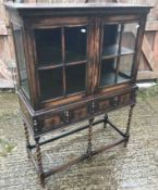 An early 20th Century oak display cabinet in the 17th Century style, the two glazed and barred doors