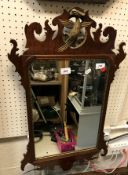 A mahogany and gilt framed wall mirror in the 18th Century manner with fretwork edge and hoho bird