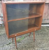 A 1960's oak display cabinet with two pairs of sliding glass doors, raised on splayed turned