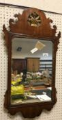 A 19th Century mahogany and gilt framed wall mirror with fretwork carved edge and floral motif to