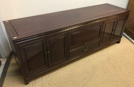 A modern Chinese rosewood sideboard, the plain top above two banks of cupboard doors flanking a