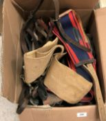 A suitcase containing various leather pony tack and a box of various tack including girths, bridles,