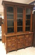 A Victorian oak and burr oak bookcase cabinet, the upper section with three glazed doors over a