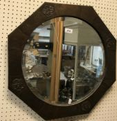 A Liberty style beaten copper octagonal wall mirror with central bevel edge plate, the frame with
