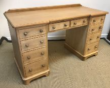 A pine dressing table / pedestal desk, the plain top with galleried back, raised on two banks of