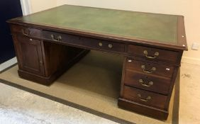 An Edwardian mahogany partners' desk, the plain top with leather insert writing surface, over two