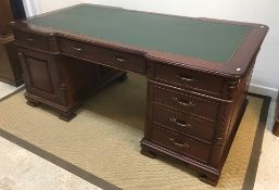 A modern mahogany partners' desk, the top with leatherette insert above a base with reeded column