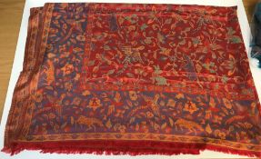 A modern shawl with floral and animal design on a red and blue ground, approx 204 cm long x 150 cm