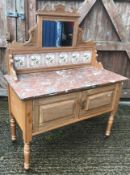A late Victorian satin walnut washstand with mirrored and tiled back over a marble top and two