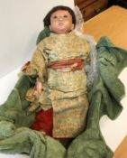 A late 19th / early 20th Century Japanese composition doll with flesh colour painted face and real