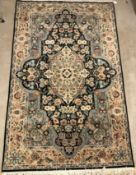 A Persian rug, the central panel set with floral decorated oval medallion on a dark blue and pale