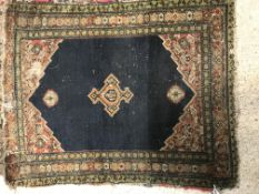 A Shenna rug, the central panel set with three medallions on a dark blue ground, within a red floral