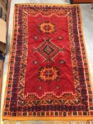 An Indian carpet, the central panel set with three medallions on a red ground, within a stepped red,