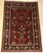 A Kashan prayer rug, the central panel set with Mirhab design with vase of flowers to base, on a red
