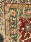 A Ziegler design carpet, the central panel set with all-over scrolling foliate decoration on a red