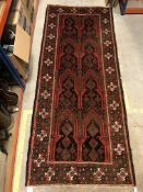 A Persian carpet, the central panel set with repeating arch decoration on a black and red ground,