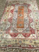 A Caucasian rug, the central panel set with three medallions on an orange and cream geometric