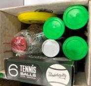 A box containing various tennis balls, squash balls, hockey balls, etc