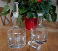 Pair of circular, clear glass decanters,