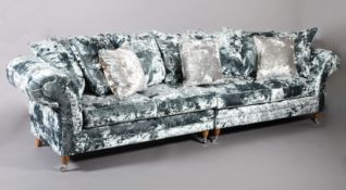 A four seater sofa upholstered in pale blue crushed velvet, on turned legs with chrome castors,
