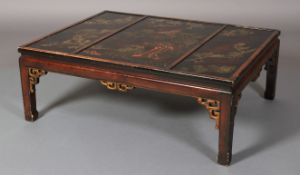 A chinoiserie black lacquered and gilt coffee table, rectangular the triple panelled top painted