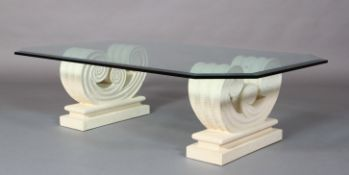 A bevelled glass coffee table on cast stone-effect twin scroll base, rectangular with cut corners,