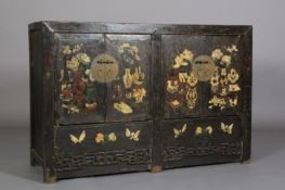 A Chinoiserie ebonised cabinet having two pairs of doors decorated with archaic symbols with brass