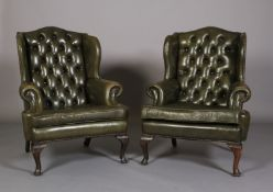 A pair of button back green leather winged armchairs, with close nail studding, on cabriole legs