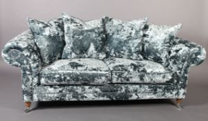 A three seater sofa upholstered in pale blue crushed velvet, on turned legs with chrome castors,