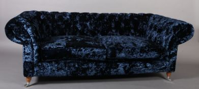 A three seater sofa upholstered in royal blue crushed velvet, on turned legs with chrome castors,