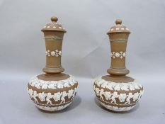 A pair of Doulton silicon ware bottle vases and covers with buff bodies, relief decorated with bands