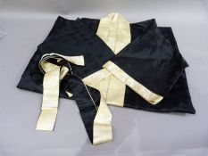 A Japanese black and pale gold kimono embroided in gilt thread with chrysanthemum