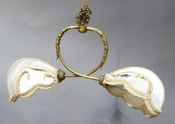 Early 20th century gilt metal twin pendant light, the crossover arms leaf capped and leaf terminal