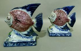 A pair of Portuguese Alcobaca pottery fish ornaments decorated with black scaled pink bodies, blue