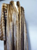 A mink coat by Busvines of London & Paris, having a stand up collar and slit pockets, approx size
