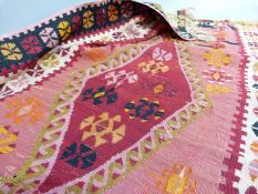 A Kilim, the pink ground woven in green, red, orange and black with three diamond motifs to the