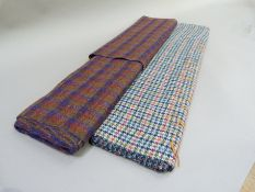 A length of Harris tweed in red and navy check and another length in green, blue and red check on