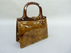 A tortoiseshell effect patent leather handbag retailed by Harrods, London, with faux shell frame and