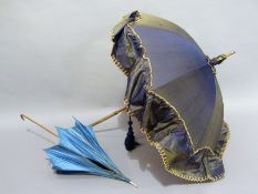 A Late Victorian blue and cream satin parasol with slender bamboo handle and turned bone tip;