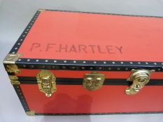 Large red and black trunk, modern, 92cm wide x 49.5cm deep x 35cm high, named P.F. Hartley