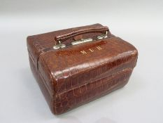 An early 20th Century crocodile skin beauty case of Gladstone style, initialled M.L.H in gilt, the