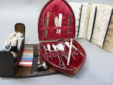 An Edwardian leather shield shape case containing mother of pearl handled stiletto's and hook,