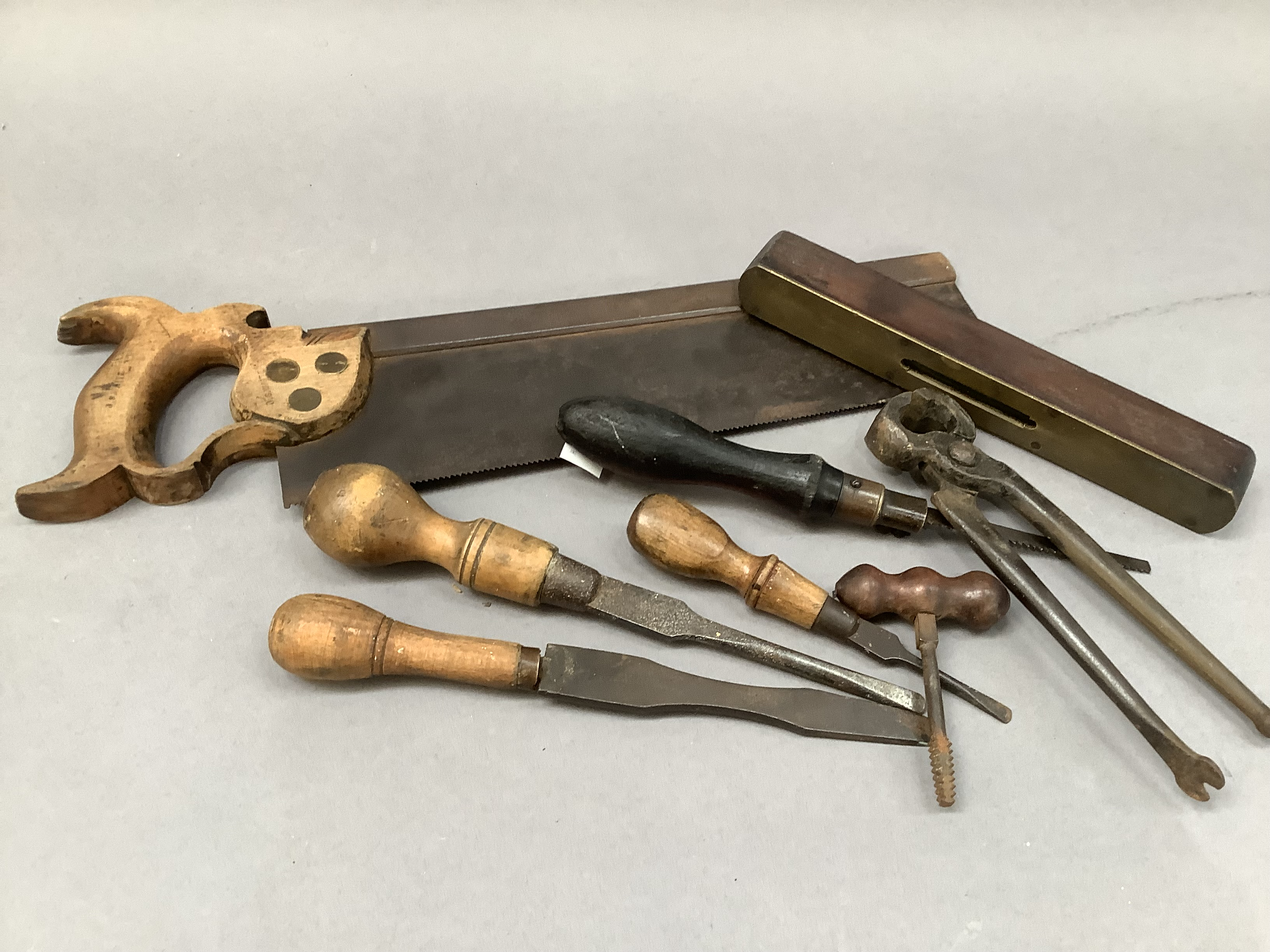 A quantity of vintage hand tools including saw, pliers, screwdrivers, level and hammer