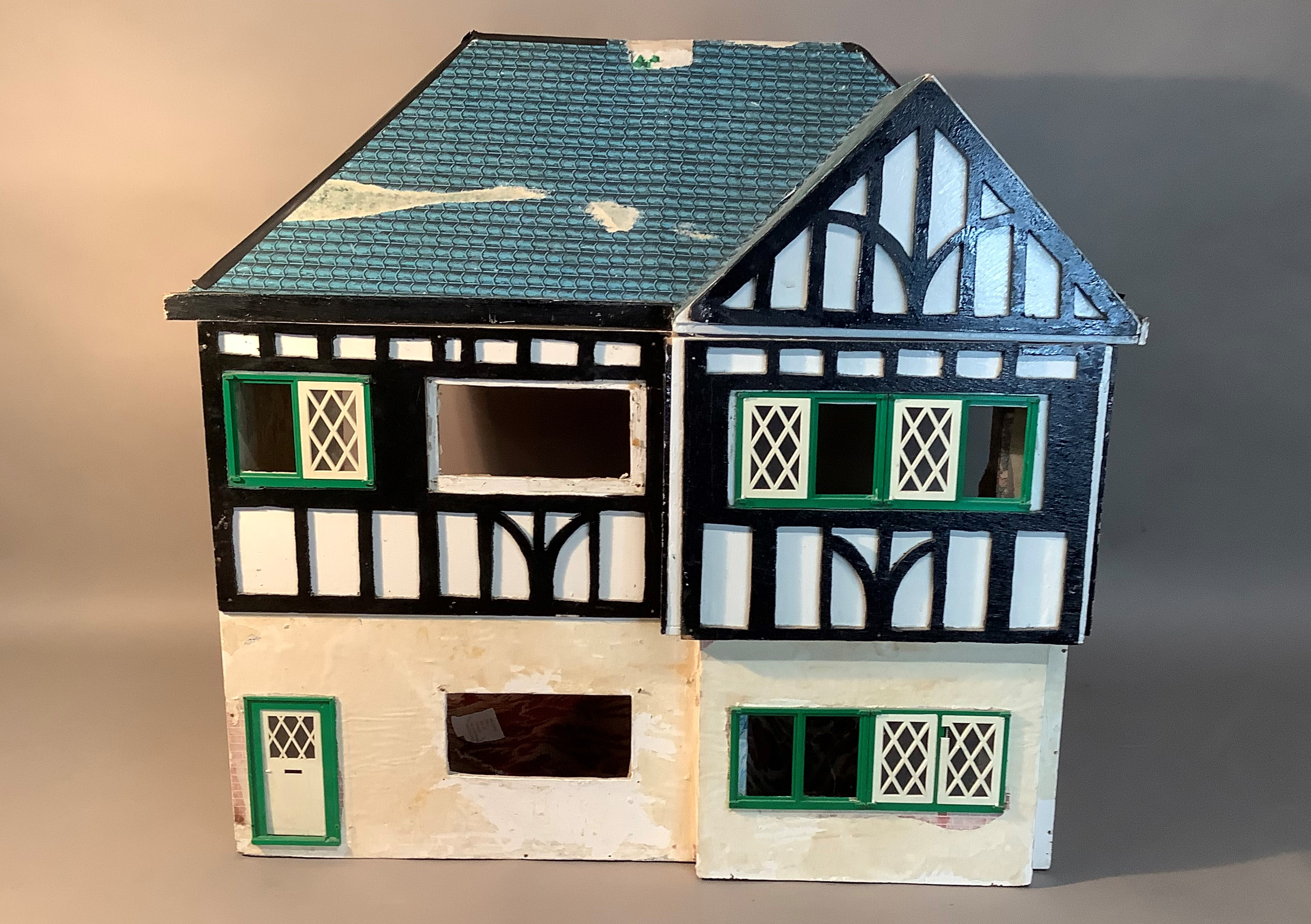 A Tudor style painted wooden dolls house with blue tiled roof, green and crème windows, 65cm wide