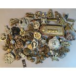A quantity of regimental badges and buttons to include West Yorkshire, Royal Norfolk, Cameron,