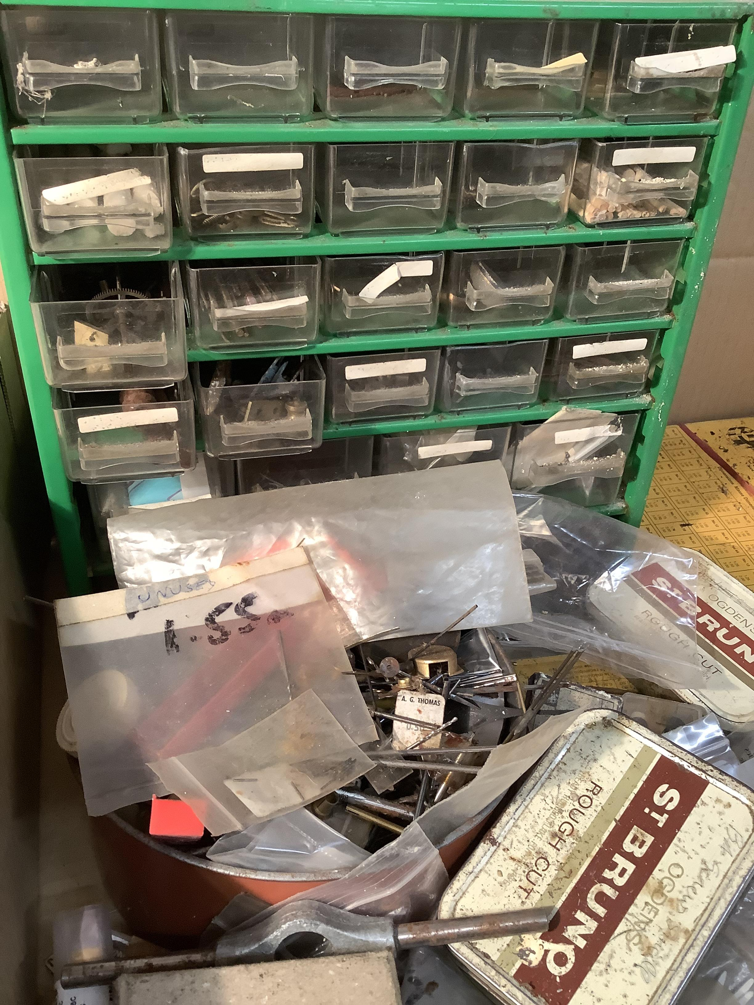 A quantity of horological spares including brass bushes, brass pin, case screws and parts, clock