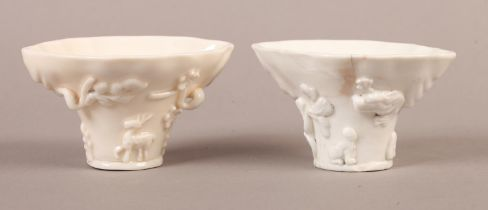 A Chinese blanc de chine libation cup, modelled in relief with dog and dragon issuing from a