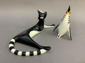 A Cmielow china figure of a black and white cat reclining, 12.5cm high by approximately 30cm long