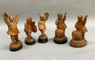 A set of five Chinese fruitwood carvings of children playing various instruments, each raised on a