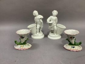 A pair of continental porcelain figures, fisherboys, each standing beside an open basket, 18cm high;